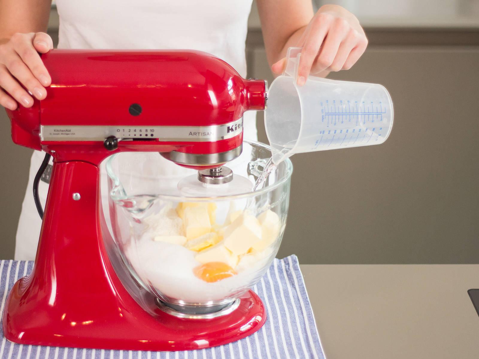 Einen Teil der Butter in große Stücke schneiden und zusammen mit dem Großteil des Mehls, Eigelb, Salz und Zucker in eine Küchenmaschine geben. Ca. 2 – 3 Min. rühren, bis sich ein krümeliger Teig gebildet hat. Anschließend langsam Wasser hinzugeben und weitere 1 – 2 Min. rühren, bis der Teig glatt und ebenmäßig ist. Teig in Frischhaltefolie wickeln und für ca. 1 Std. in den Kühlschrank geben.