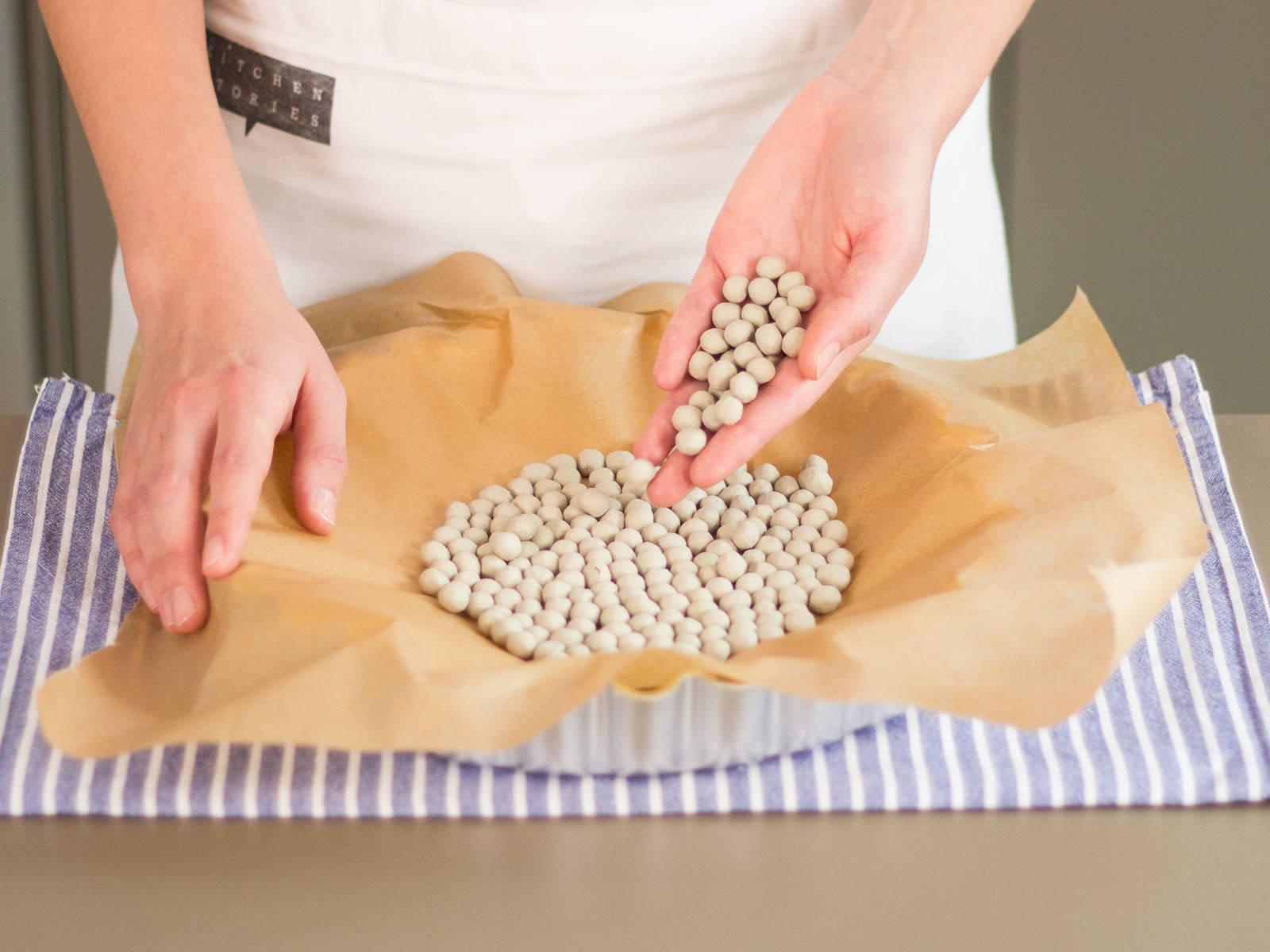 Beide Seiten des Teigs mit Mehl bestäuben und in die Pie-Form legen. Gleichmäßig an den Rand andrücken und überschüssigen Teig entfernen. Backpapier über den Teig legen und mit Backkugeln beschweren. Im vorgeheizten Backofen bei 180°C ca. 10 Min. backen.