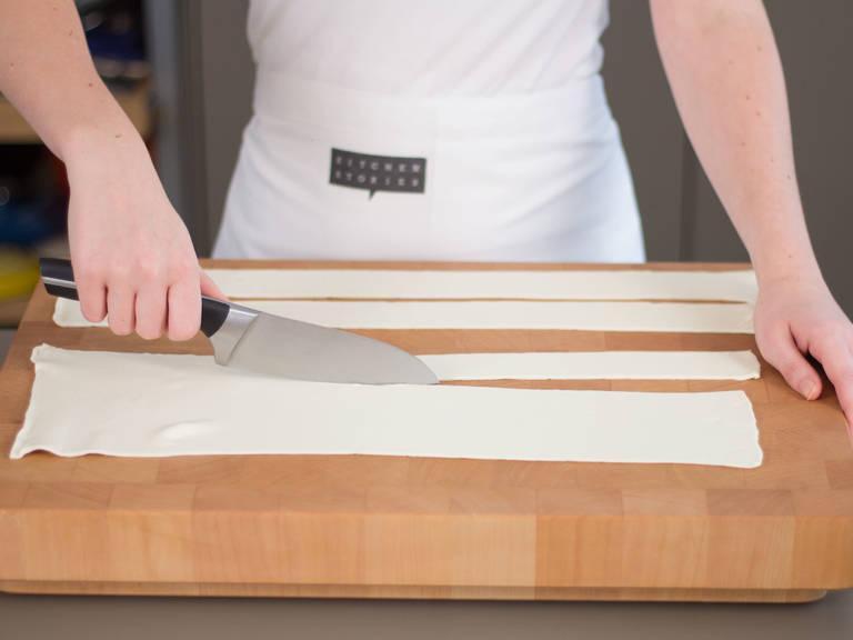 将烤箱预热至190摄氏度/375华氏度。 将酥皮铺平,切成约4指宽的条状。