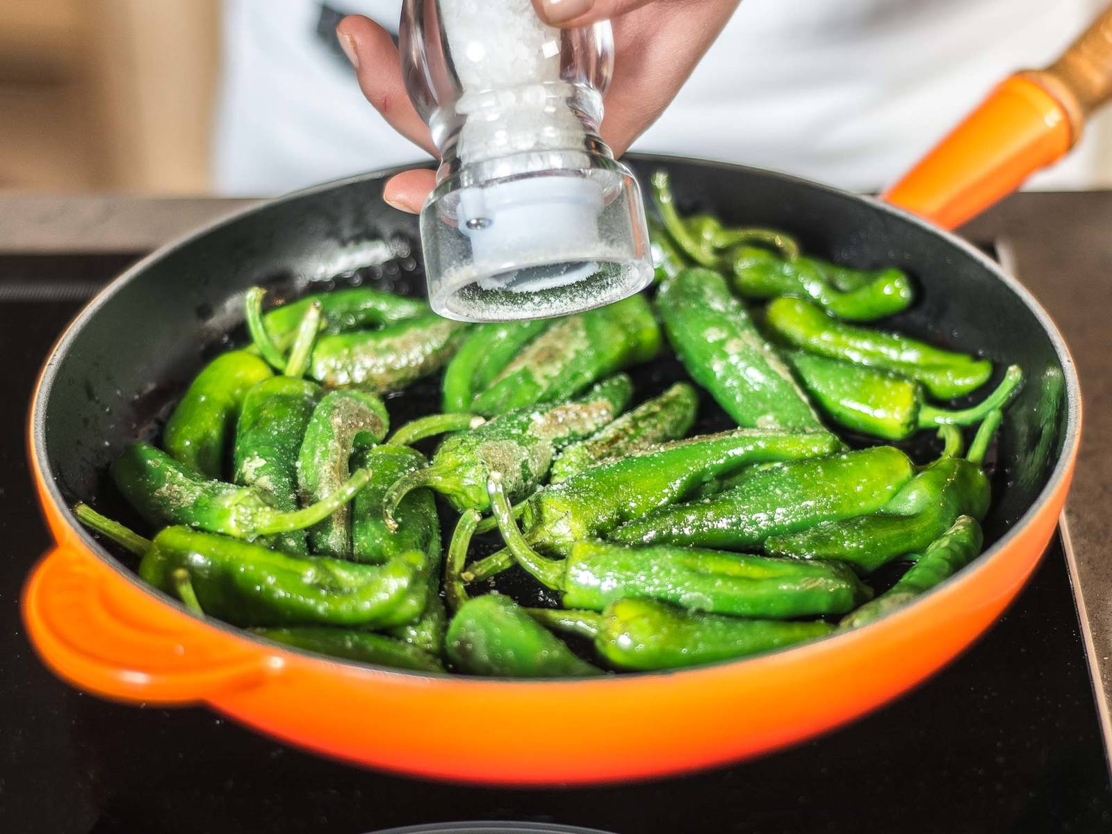 In a second pan, fry Padrón peppers in some vegetable oil and add plenty of salt. Toss the noodles in the sauce and serve in a deep dish with the fried Padrón peppers on top.