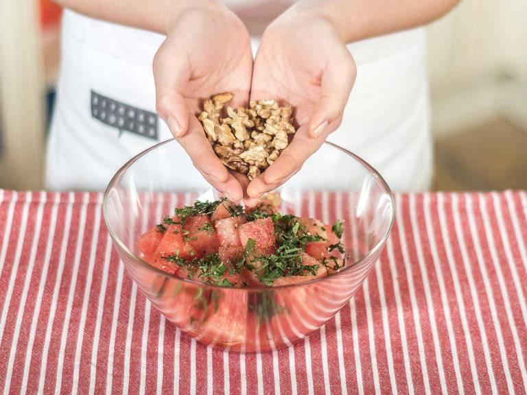 Walnüsse mit den Händen leicht auseinander brechen und zur Wassermelone geben.