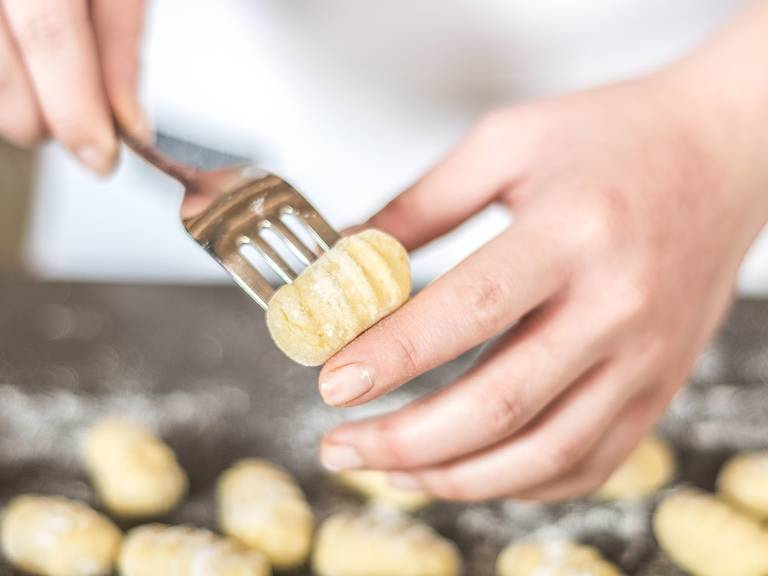 Transfer the dough to a lightly floured work surface. Make long rolls out of the dough. Using a knife, cut dough into large pieces approx 1cm x 2cm large. Roll these pieces over a fork to create the traditional gnocchi appearance.