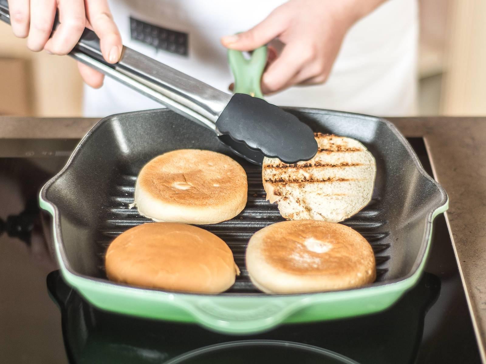 Burger-Brötchen in einer Pfanne von beiden Seiten toasten. Die untere Hälfte des Burger-Brötchens mit Salat belegen. Darauf die Gemüsemasse verteilen und abschließend die obere Burgerhälfte auflegen.