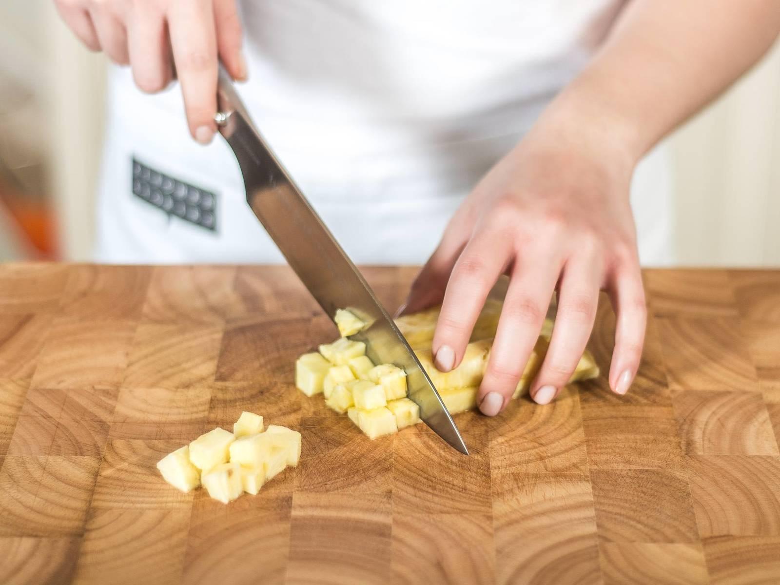 In der Zwischenzeit Ananas schälen, den Strunk entfernen und das Fruchtfleisch in kleine Würfel schneiden.
