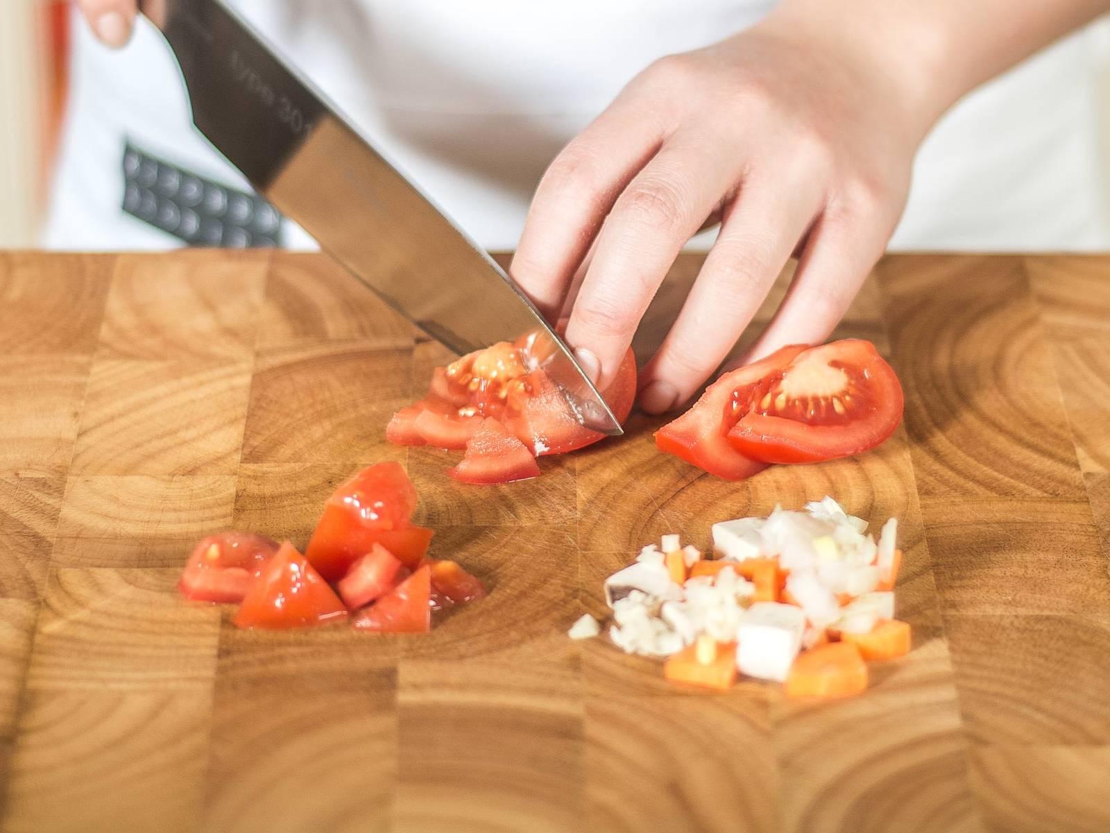 Für die Soße eine Zwiebel, eine halbe Knoblauchzehe, Champignons, Tomaten und die Karotte würfeln.