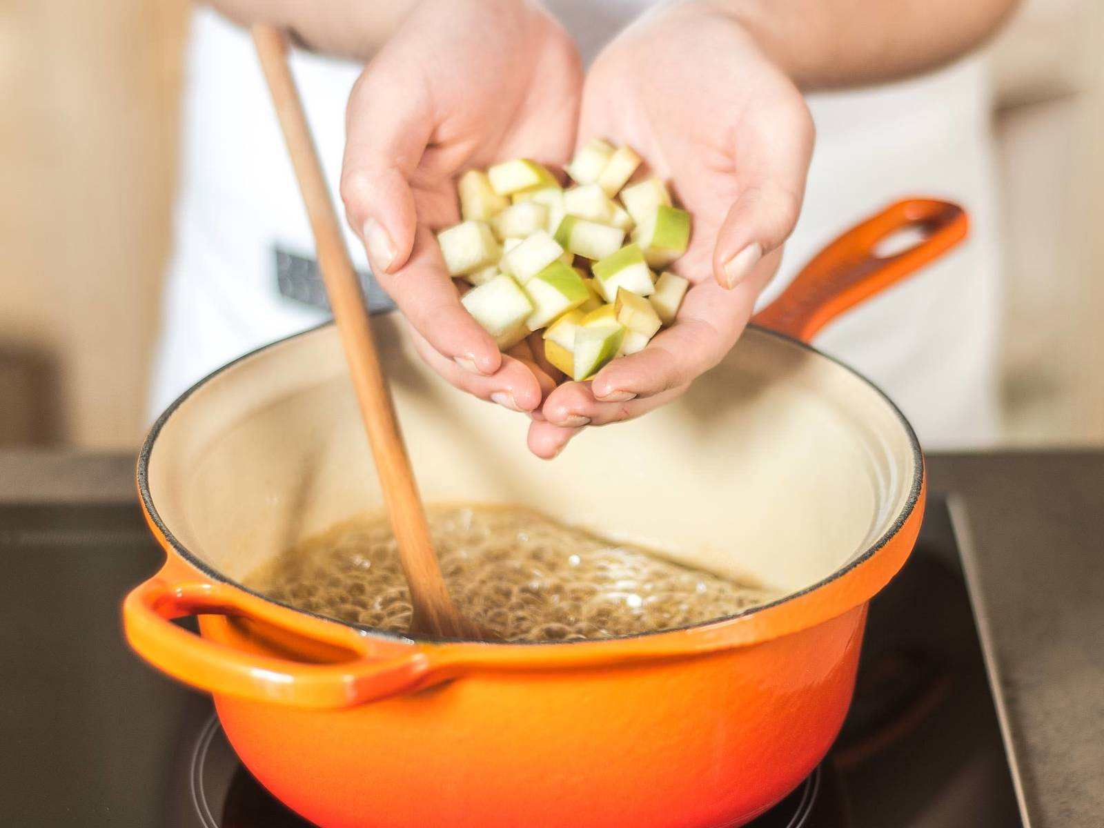 再加入苹果块、肉桂和一小撮盐,继续用中温煮5-10分钟至水果软化。