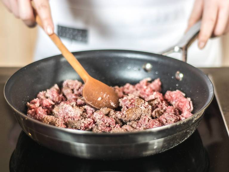 In another pan, sear ground beef with some vegetable oil. Season with salt and pepper. As soon as the meat has browned add it to the vegetables and bring to a gentle boil.