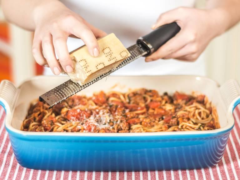 把意大利面条放入深烤盘中,淋上酱汁,拌匀。然后撒上帕玛森干酪碎。放入已预热至160摄氏度的烤箱中烤约7分钟。从烤箱取出即可享用。