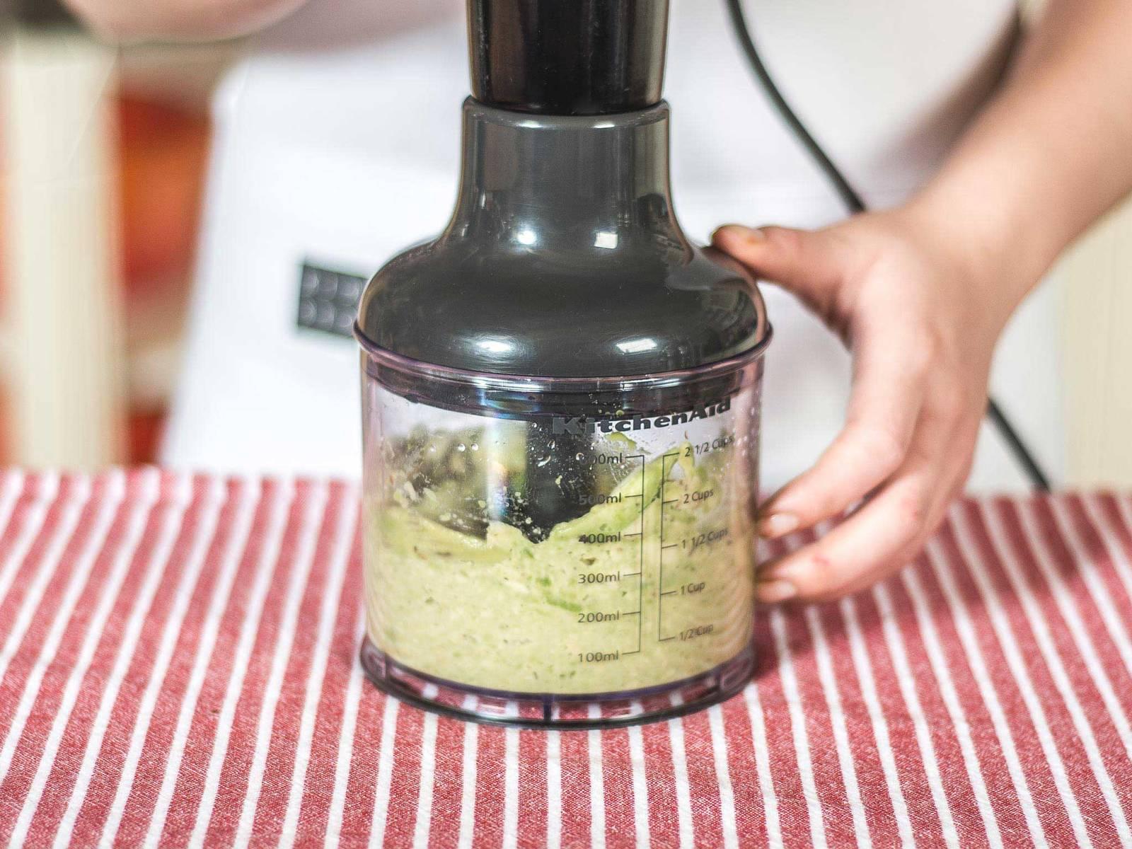 用食品加工机将鳄梨、柠檬汁、盐和胡椒打成泥。香菜切碎,拌入鳄梨混合料中。