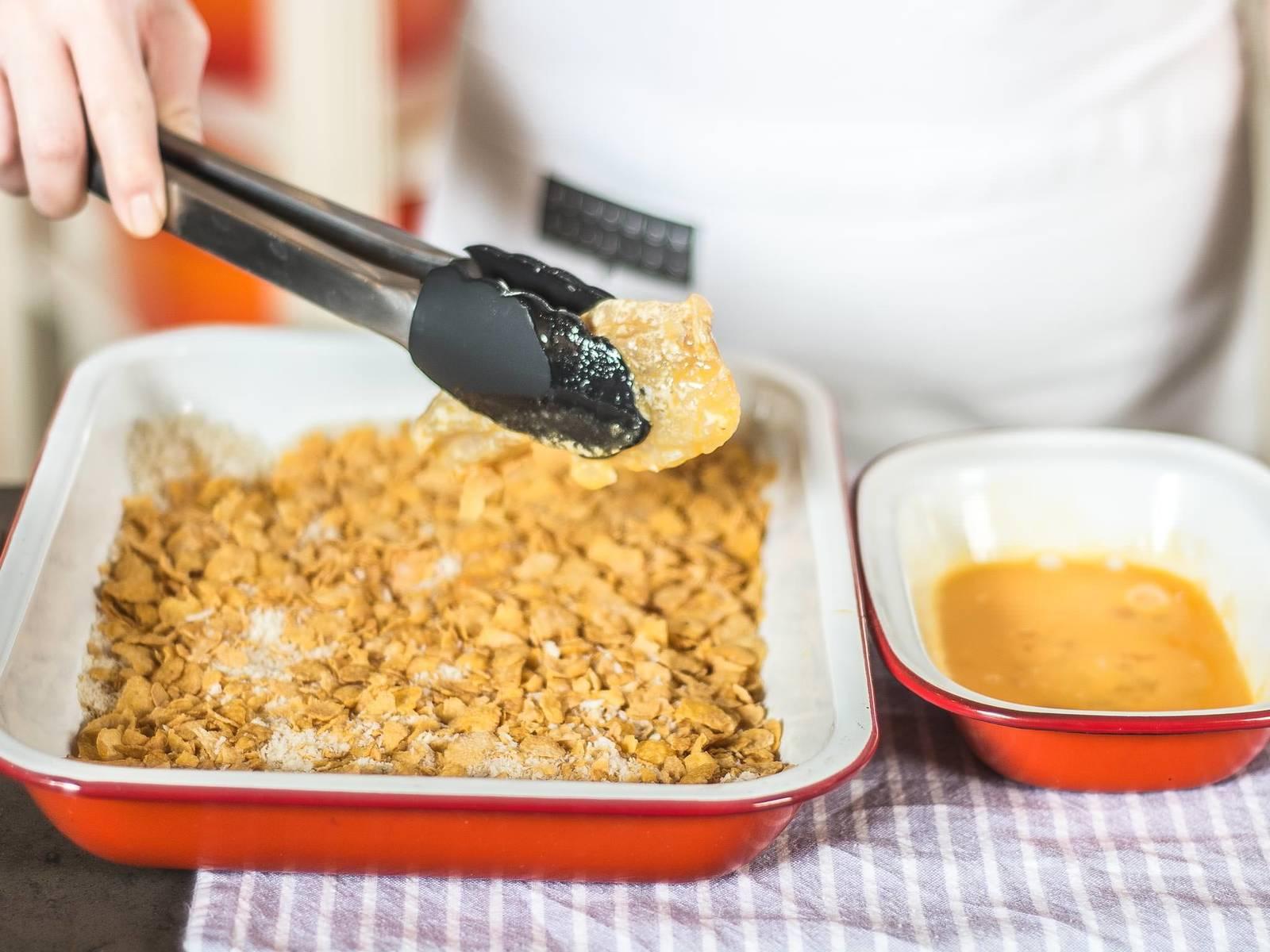 Kabeljau salzen, pfeffern und jeweils durch die drei Schüsseln ziehen. Zuerst durch das Mehl, dann durch das Ei und zum Schluss durch das Panko-Cornflakes-Mehl.