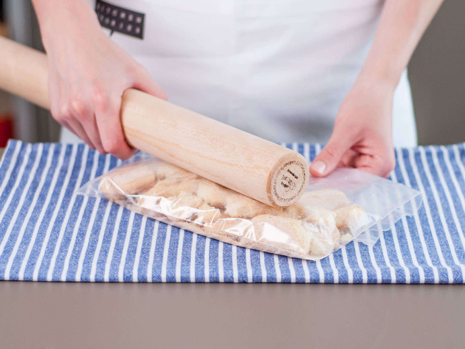 将手指饼干放入冷冻袋并密封,然后用擀面杖将饼干压碎。