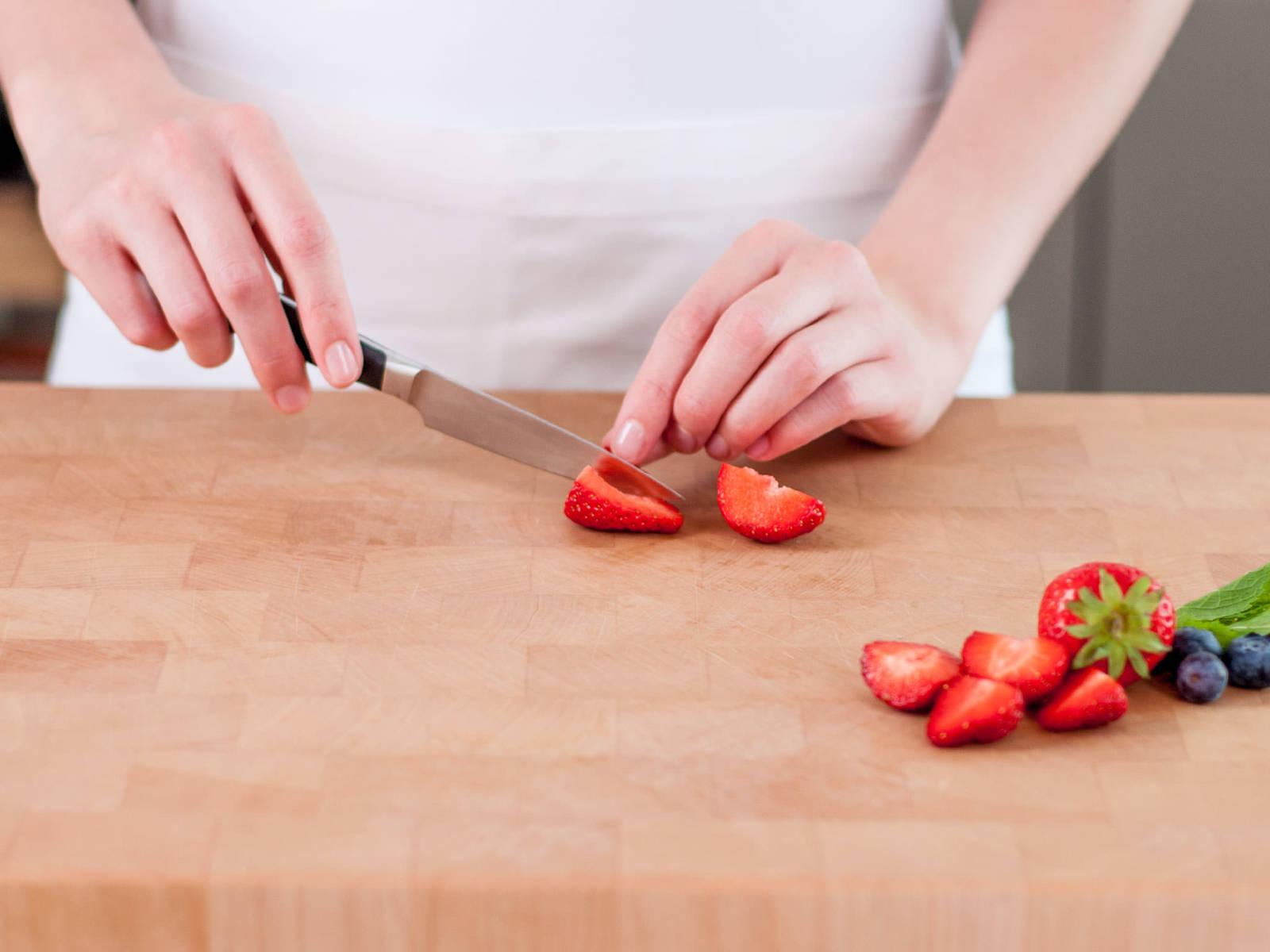 将蓝莓清洗后放置一旁备用。粗略切碎薄荷,将草莓切成四半。