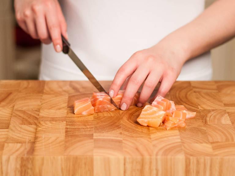 Backofen auf 200°C vorheizen. Die Lachsfilets in mundgerechte Würfel schneiden, mit Salz und Pfeffer würzen.