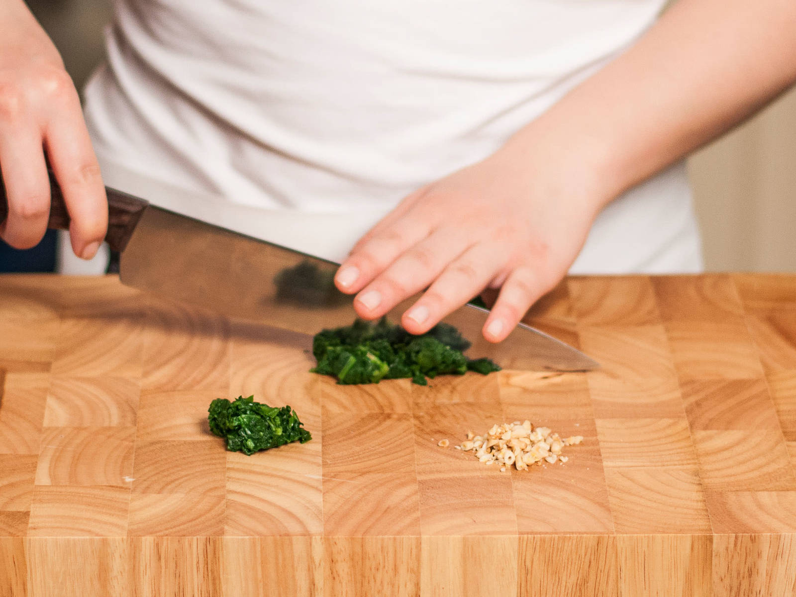 Finely chop pine nuts and blanched spinach.