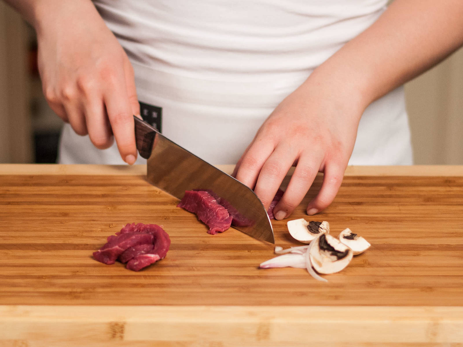这期间,将洋葱切成薄片。将蘑菇清洗干净,切成四半,牛排切成丝。