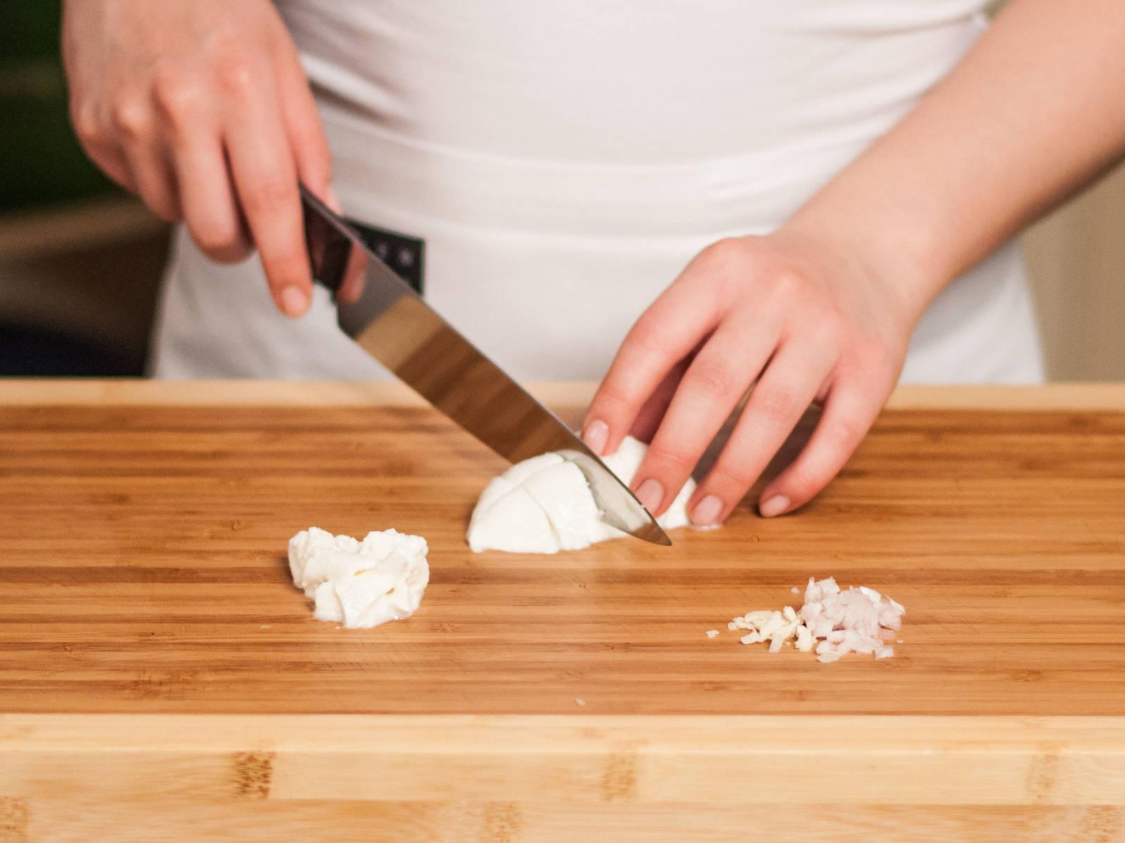 细细剁碎洋葱和蒜。将水牛乳马苏里拉奶酪切成胡桃大小。