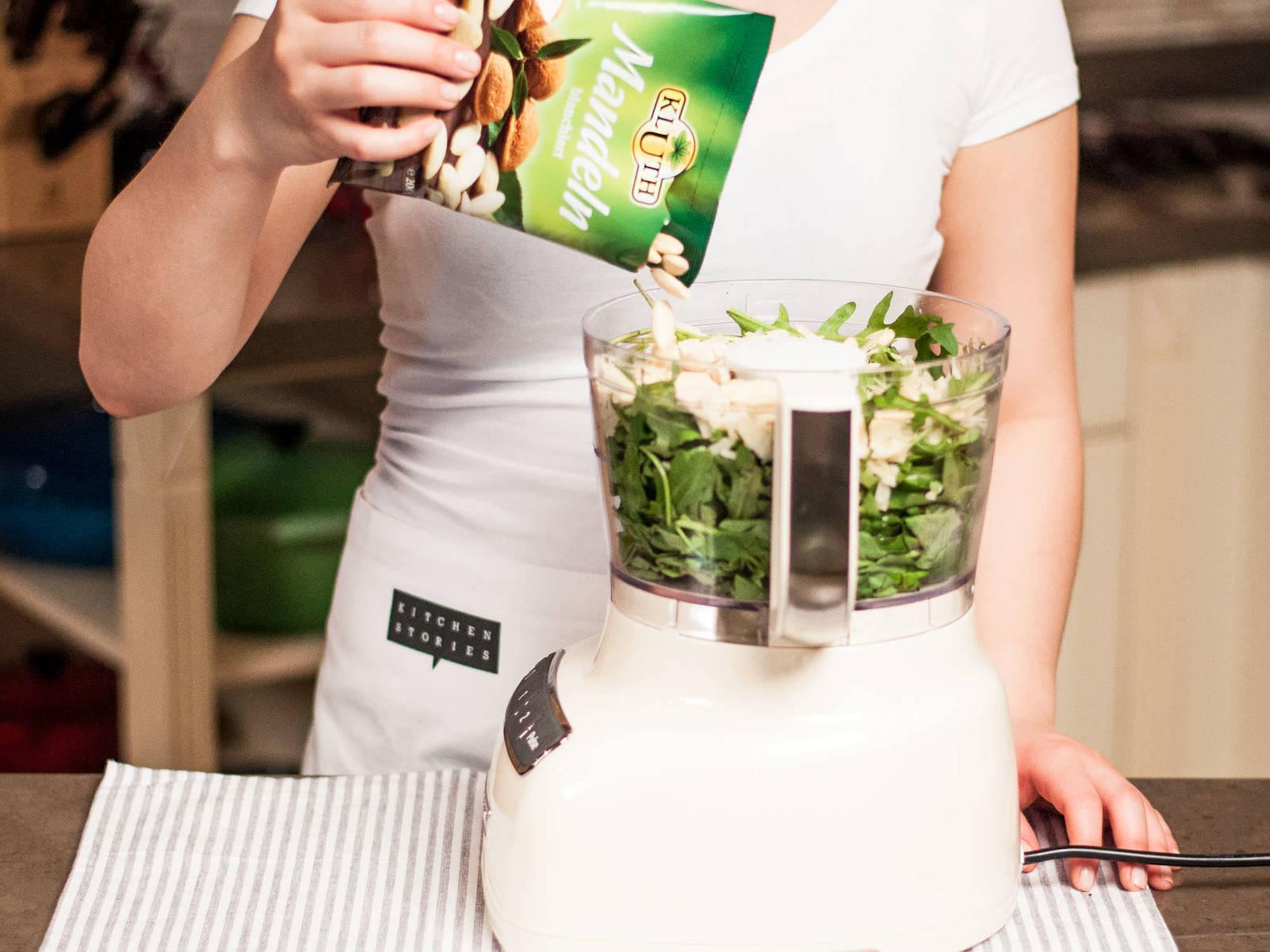 Rucola, Basilikum, Mandeln, Parmesan, Salz und Pfeffer im Zerkleinerer fein hacken.