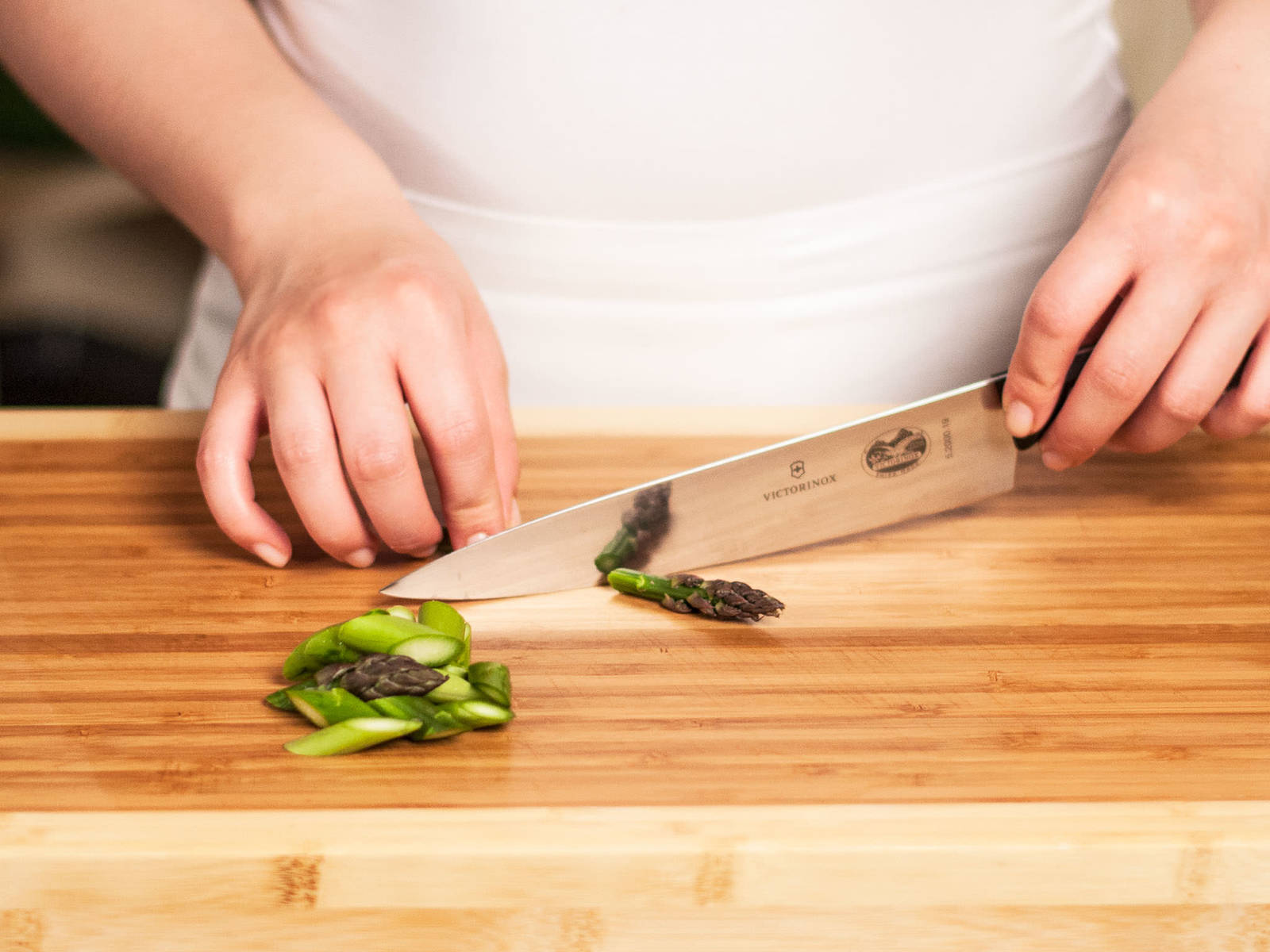 Trim wooden ends of asparagus. Then, cut into bite-sized pieces at a slight angle.