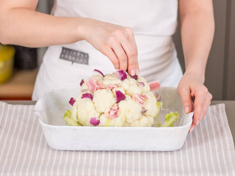Transfer cauliflower to baking dish. Stuff with bacon and red onion in between florets.