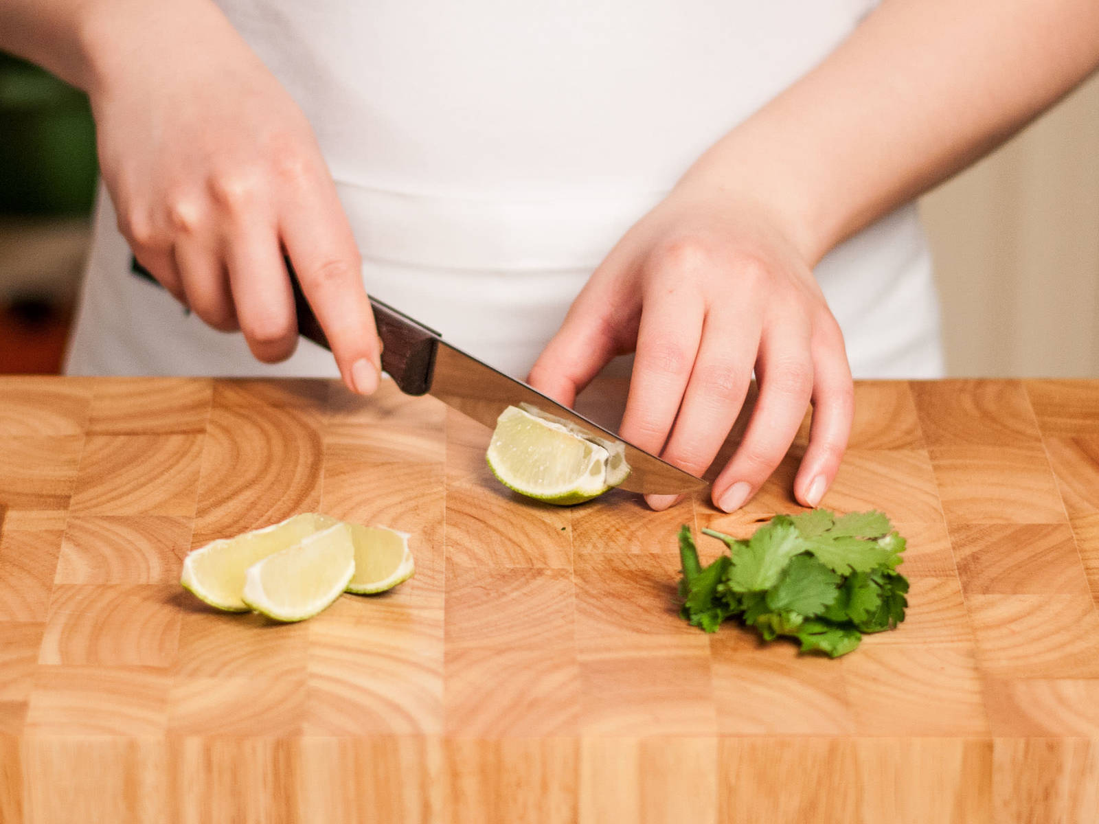 In the meantime, cut limes into wedges and pick cilantro leaves from sprig.