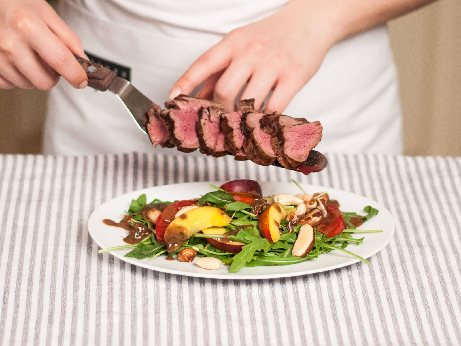 In a salad bowl, toss arugula, tomatoes, and nectarines with the dressing and place on serving plates. Slice up tenderloin and arrange on top of the salad. Sprinkle with toasted nuts and season again with salt and pepper before serving.