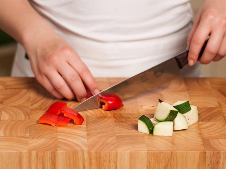 Backofen auf 200°C vorheizen. Zwiebel und Knoblauch fein hacken. Zucchini, Aubergine und Paprika in mundgerechte Würfel schneiden.