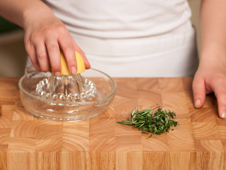 Saft der Zitrone auspressen und Thymian sowie Rosmarin jeweils von den Stängeln zupfen.