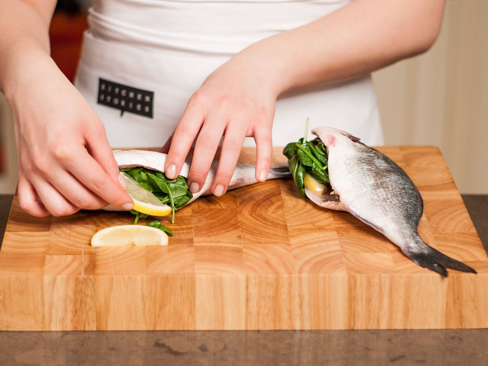 Remove fins and generously season the cavity with sea salt. Fill each gilthead with a crushed garlic clove, thyme, rosemary, baby spinach and a few slices of lemon.