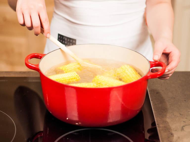 Grill vorheizen. Den Mais putzen, harte Enden entfernen und portionieren. Die Maisstücke in kochendes Salzwasser geben und ca. 15 – 20 Min. kochen.