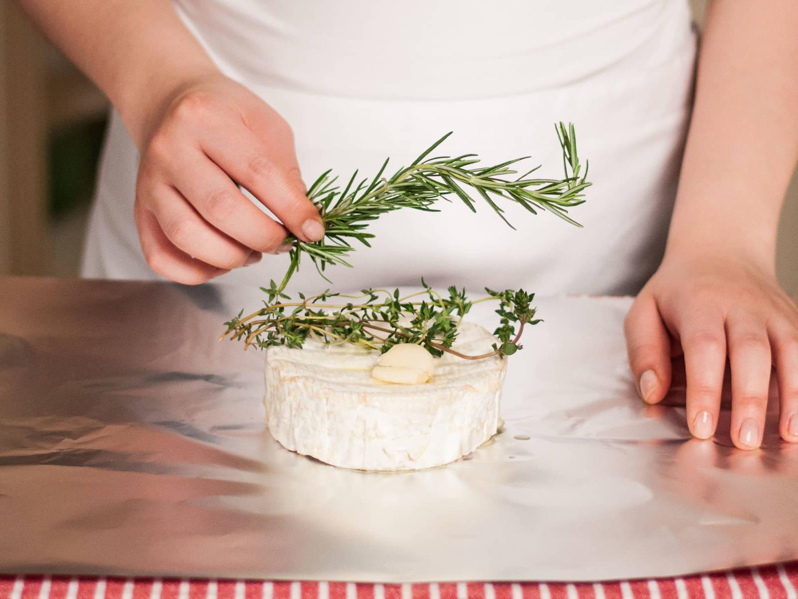 预热烤架。将卡蒙贝尔奶酪放在一块正方形的锡纸上,用橄榄油刷一遍。在上面摆放迷迭香、百里香和拍碎的蒜瓣。
