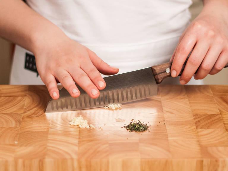 Grill vorheizen. Knoblauch schälen, grünen Trieb entfernen und zusammen mit den Rosmarin– und Thymianblättern fein hacken.