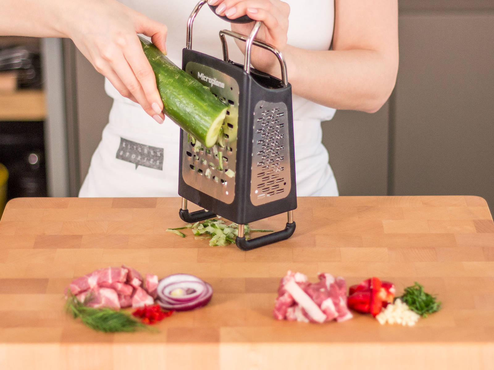 Cut meat into thin strips and onions into fine rings. Finely dice garlic and chili. Cut bell pepper into strips. Roughly chop parsley and dill. Coarsely grate cucumber using large holes of a box grater.