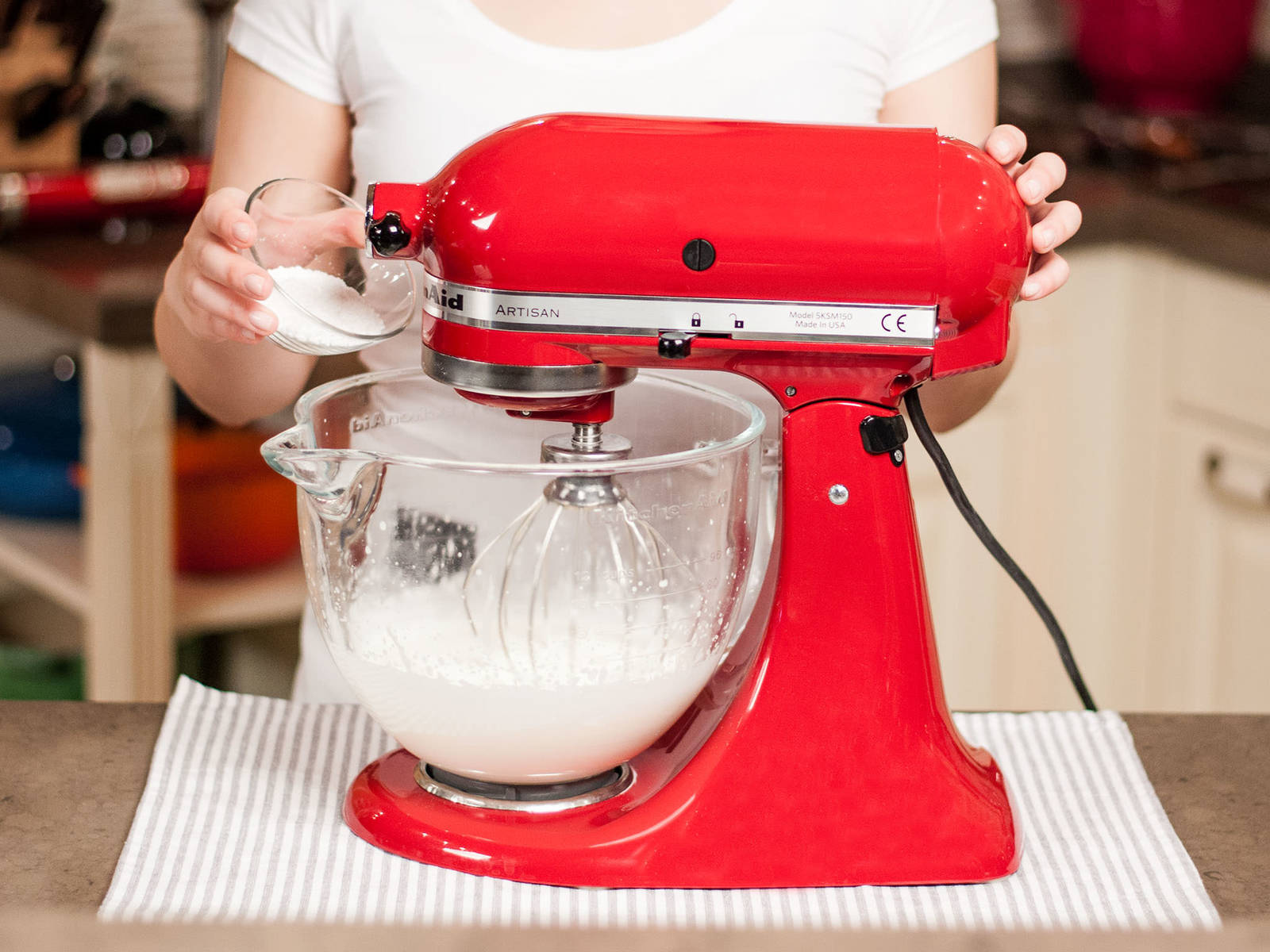 Whip cream until stiff peaks form. Add sifted confectioner's sugar towards the end and whisk in.