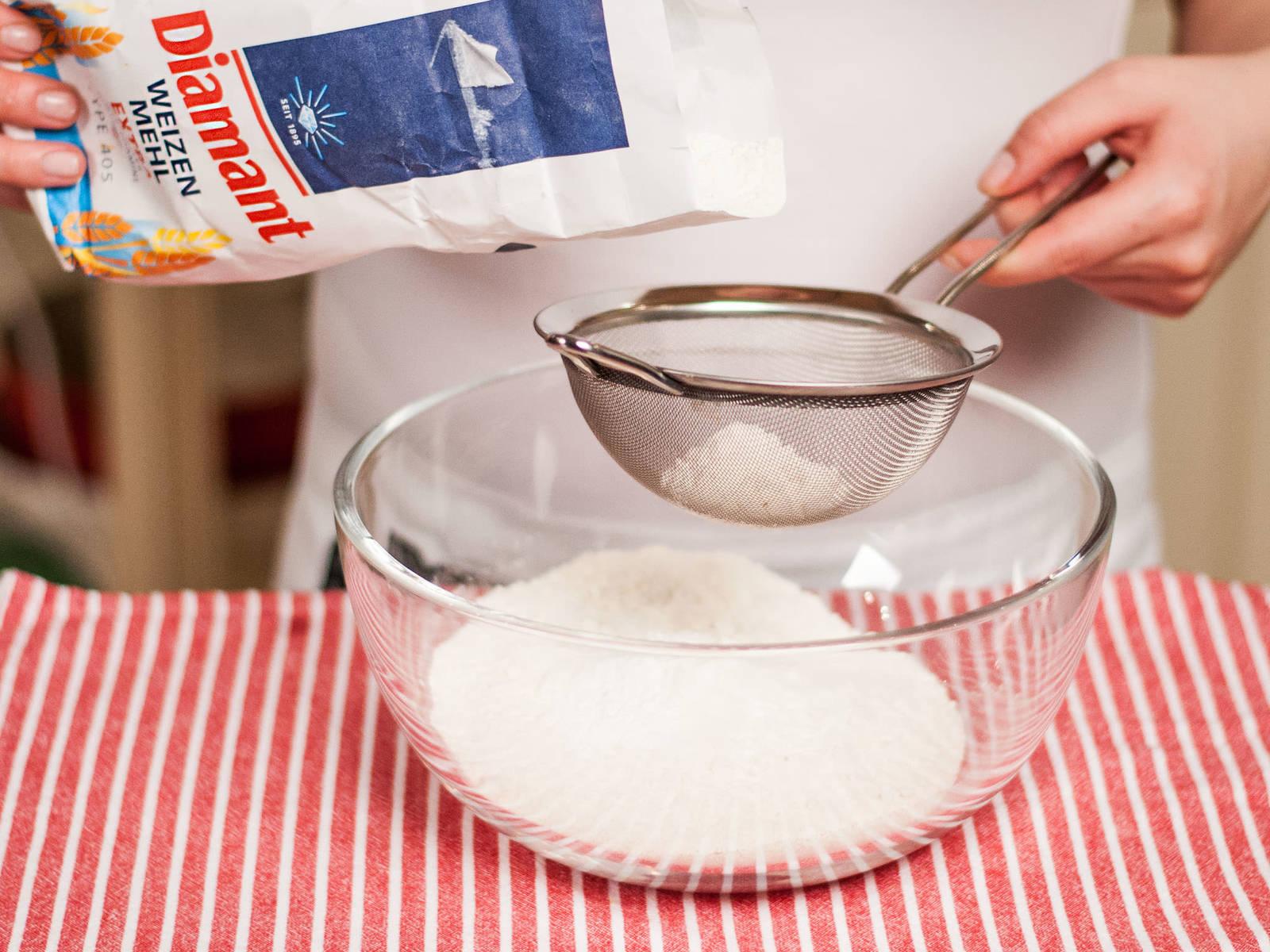 将面粉、泡打粉和盐过筛到另一碗中。倒入黄油混合物,搅打至面糊顺滑。