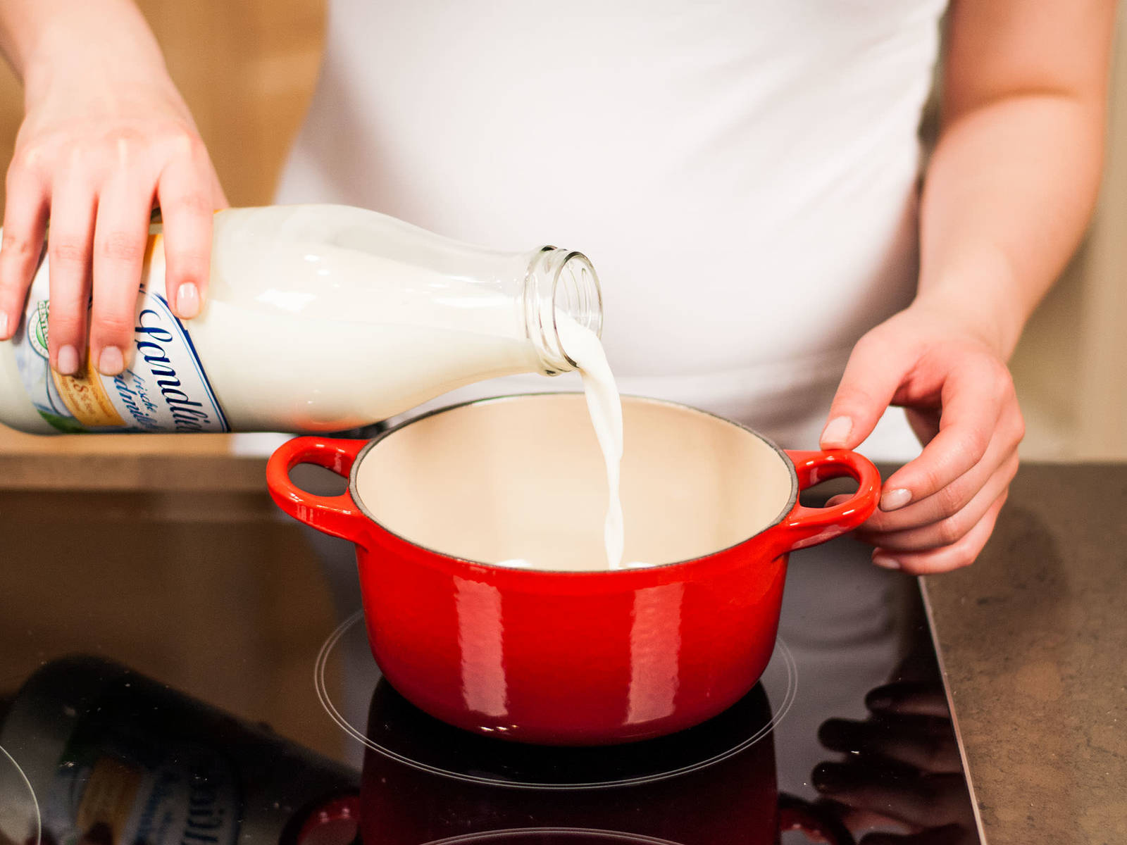 将糖加入牛奶,煮至微沸。加入做好的蛋黄糊,继续加热使其变稠,同时不断搅拌。