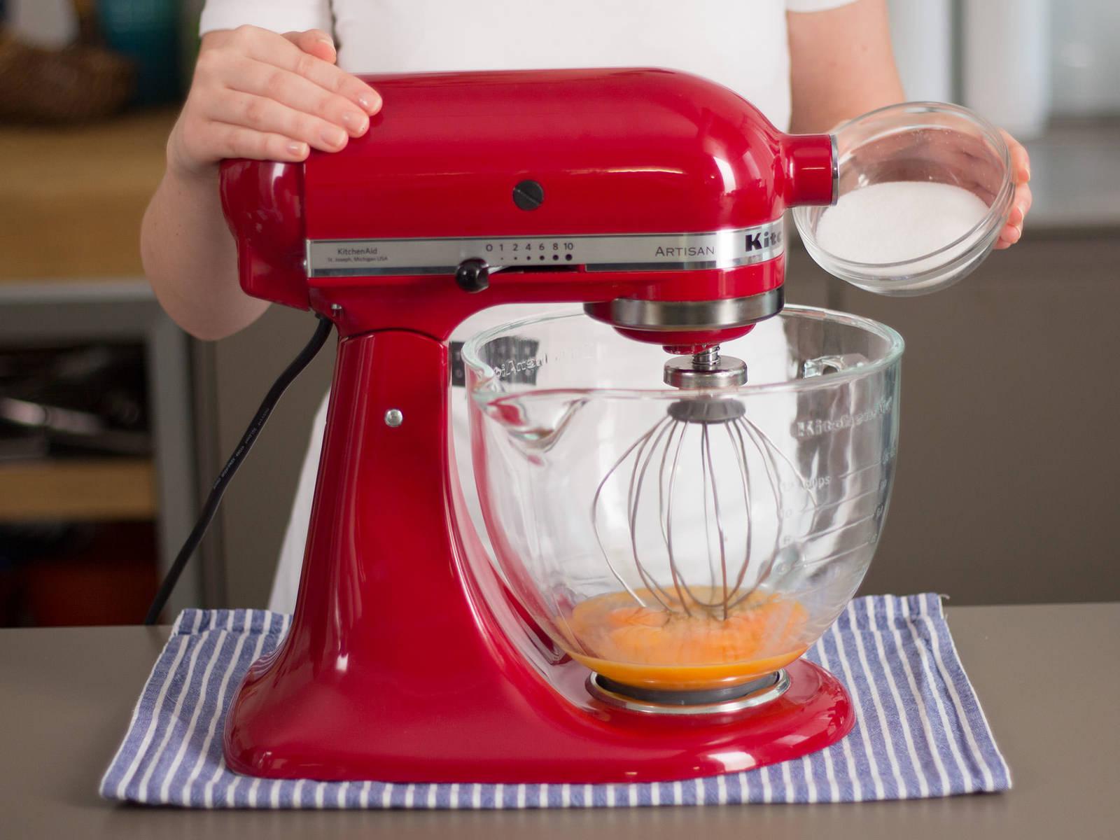 Eigelb, Eier und Zucker in einer Küchenmaschine dickflüssig aufschlagen.