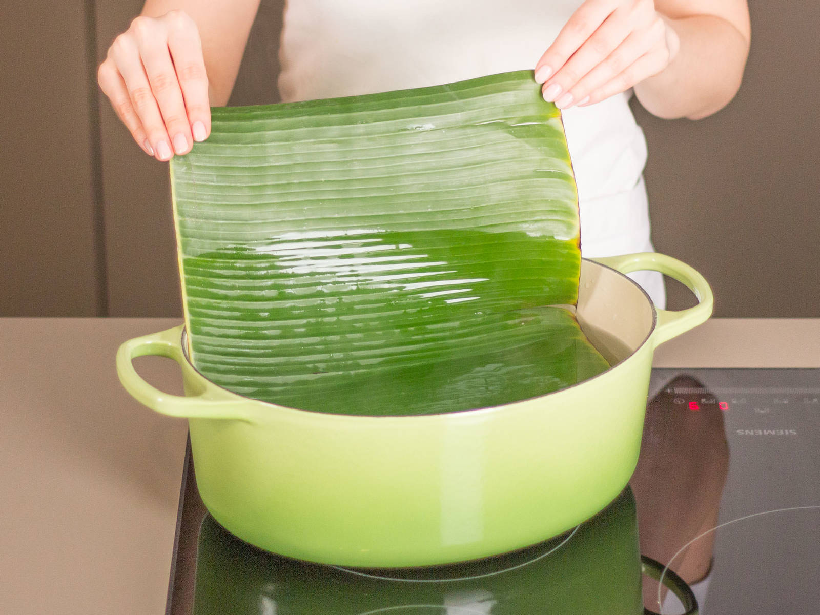 Cut banana leaves in into pieces large enough to wrap around cod pieces. Heat water in a large saucepan: do not boil. Add banana leaves one at a time for approx. 2 min., or until softened.