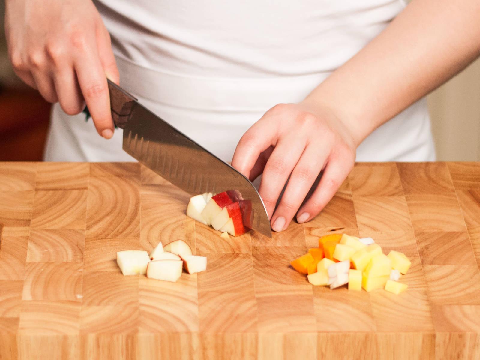 烤箱预热至200摄氏度。将土豆、胡萝卜、洋葱和苹果切成1里面见方的小块。