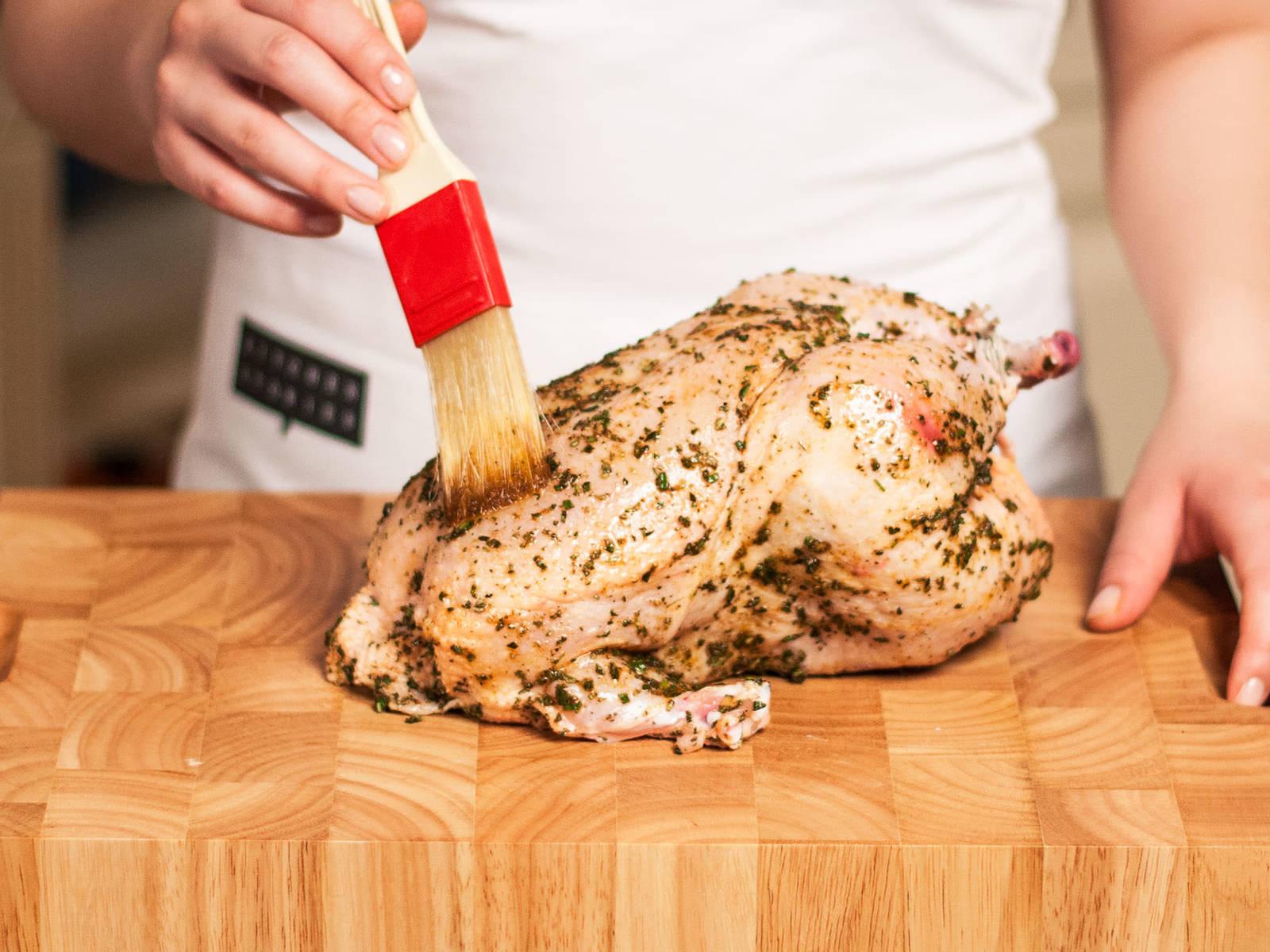 将鸡内外都刷上腌料,并向鸡肚中填入腌好的蔬菜。