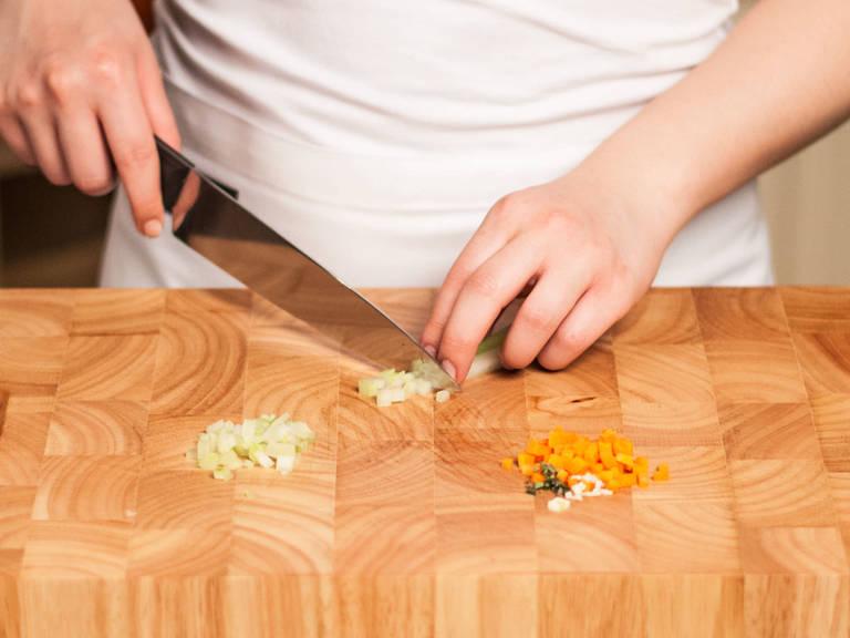 Backofen auf 200°C vorheizen. Zwiebel, Knoblauch und Thymianblätter fein hacken. Karotte schälen und in feine Würfel schneiden. Sellerie ebenso in kleine Stücke schneiden.