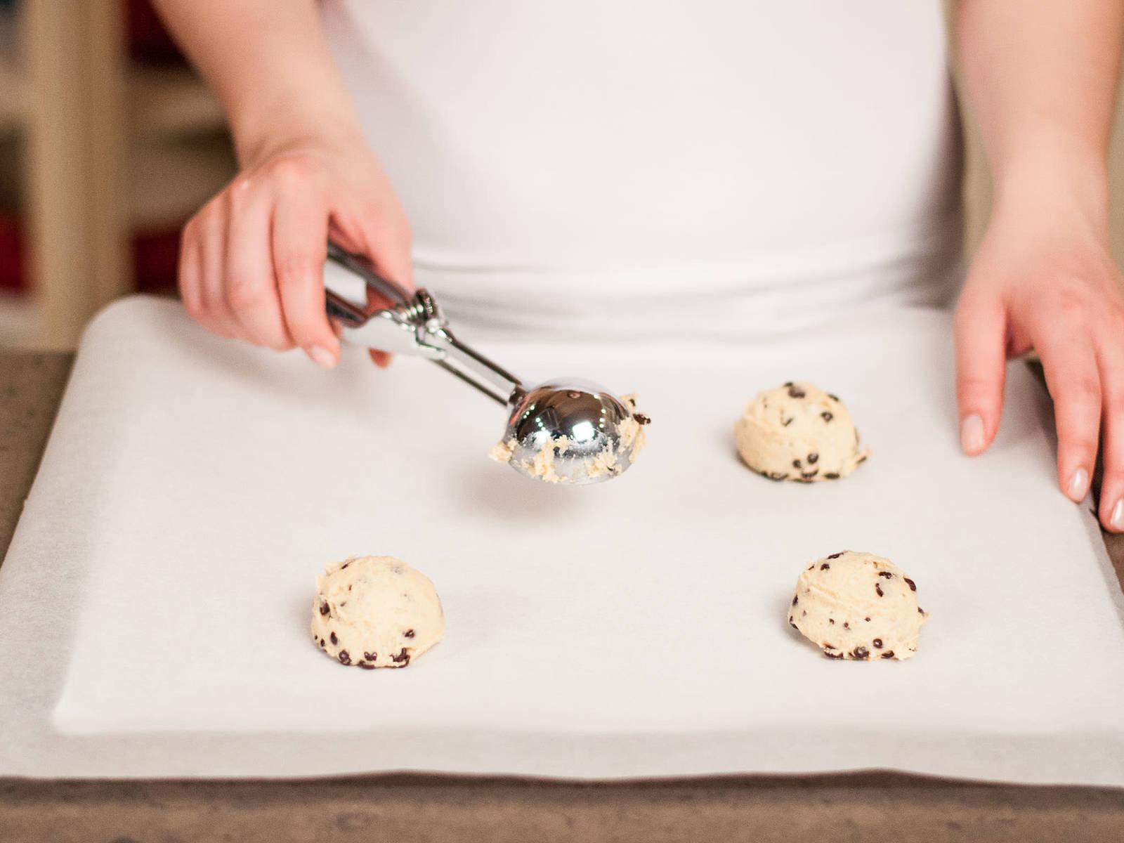 舀一勺面糊到铺好烘培纸的烤盘上,每两块饼干之间留出足够的距离,并用勺背轻轻压扁。放入预热好的烤箱中,以180摄氏度烤10-12分钟至呈金黄色。曲奇中间应是软的,冷却10分钟左右后即可享用。