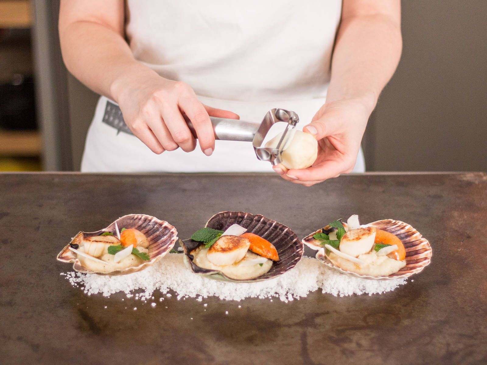 Remove leaves from cilantro and mint. Arrange sunchoke purée on a serving plate, top with scallops, and garnish with mint, cilantro, and some freshly peeled sunchokes.