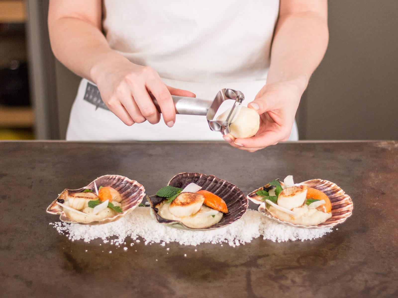 Koriander und Minze zupfen. Topinambur-Püree auf einem Teller anrichten. Jakobsmuscheln darauflegen. Mit Koriander, Minze und frisch geschältem Topinambur garnieren.