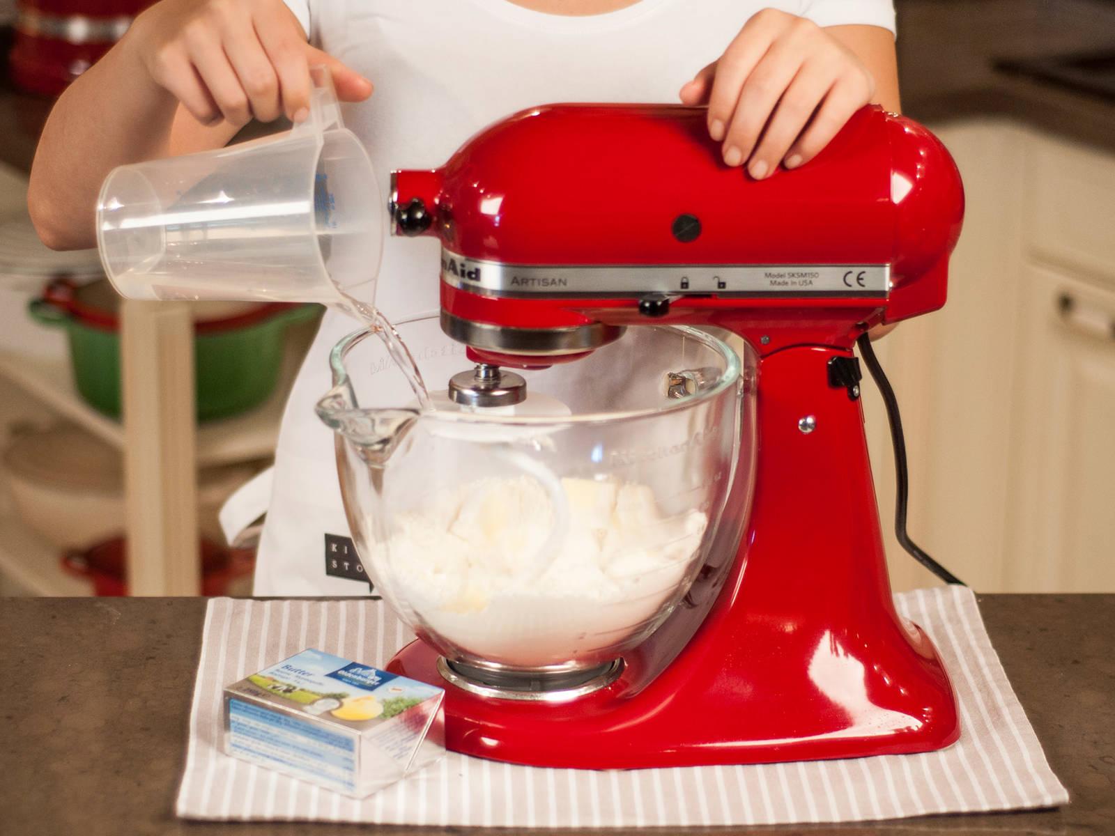制作派底:使用立式搅拌机或带和面钩的手持搅拌机将面粉、冷黄油和部分盐搅拌均匀,注入冷水搅打,然后用手将面团揉至光滑。