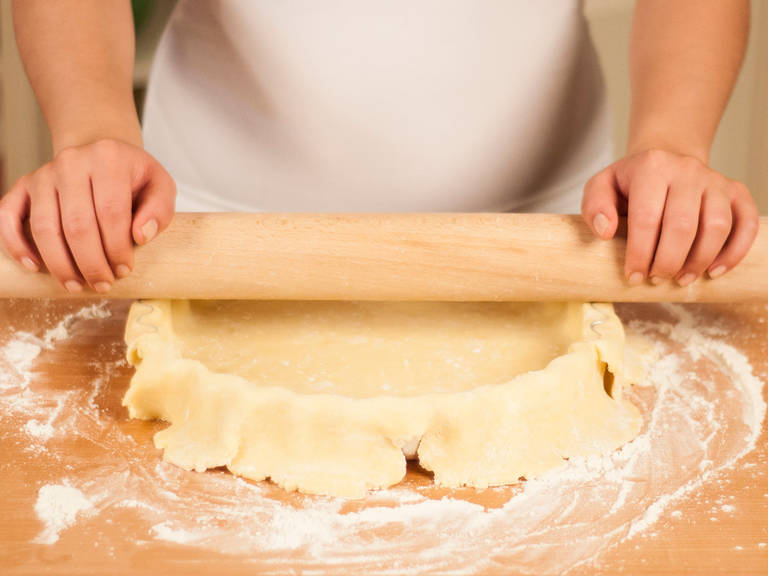 Cut off overhanging dough by rolling the rolling pin over the edges of the tart dish.
