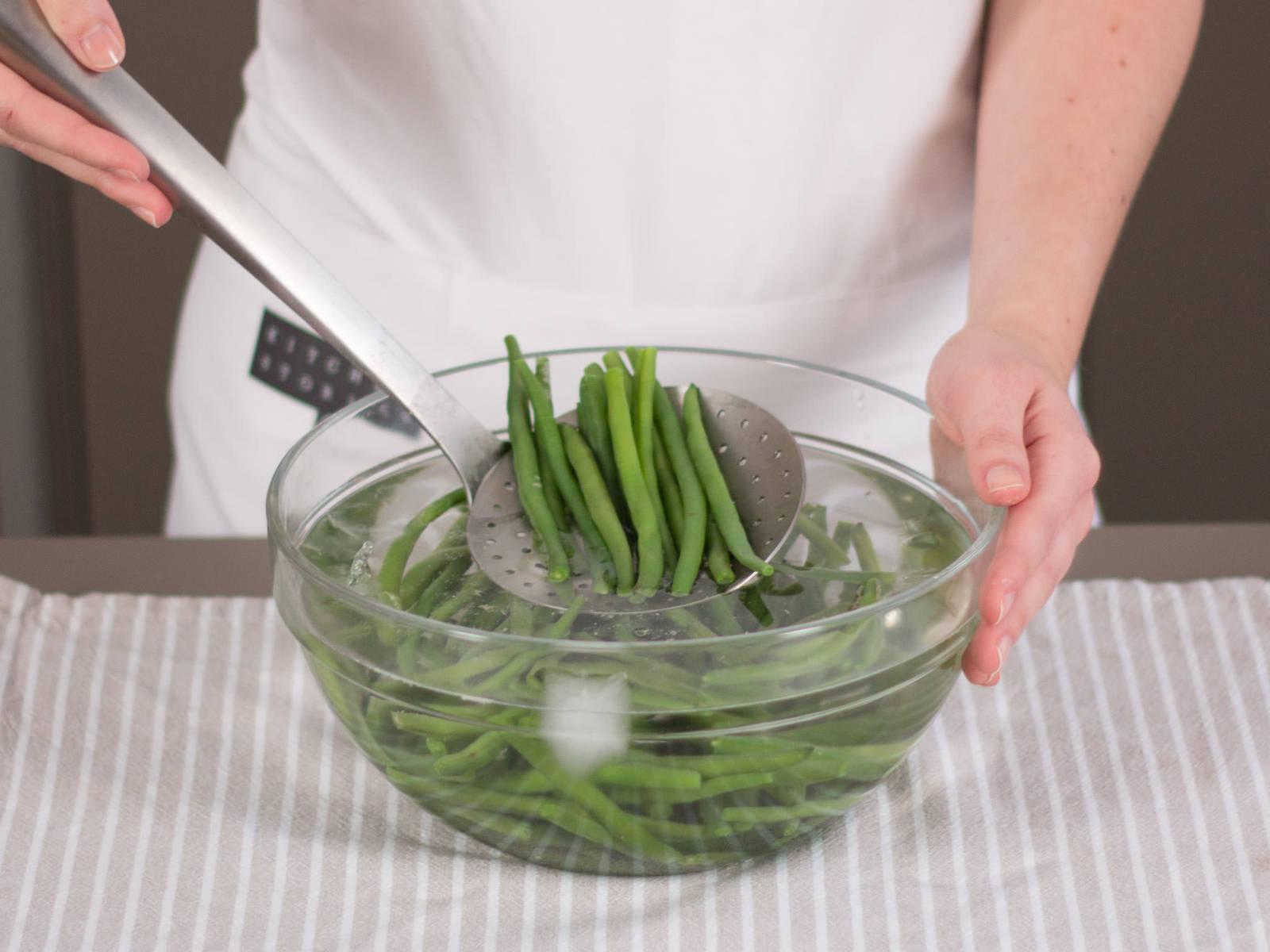 切好四季豆。可根据个人口味,将一半的夏香薄荷加入装有盐水的大锅中煮沸。将四季豆汆烫 2 分钟。然后放入加入水和冰块的大碗中。约 1 分钟后从冰水中取出四季豆,静置备用。