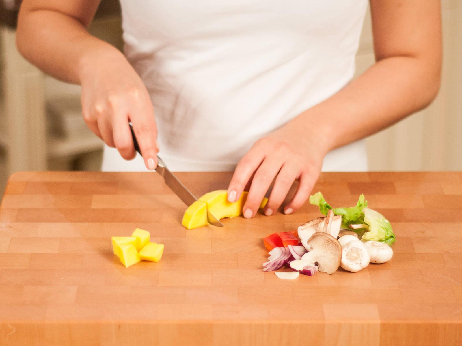 Frühlingszwiebeln in Ringe schneiden. Zwiebel und Knoblauch fein hacken. Außerdem Salat, Paprika, Waldpilze und Mango in mundgerechte Stücke schneiden.