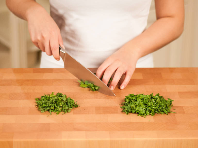 In the meantime, pick coriander, mint, and parsley leaves. Finely slice them.
