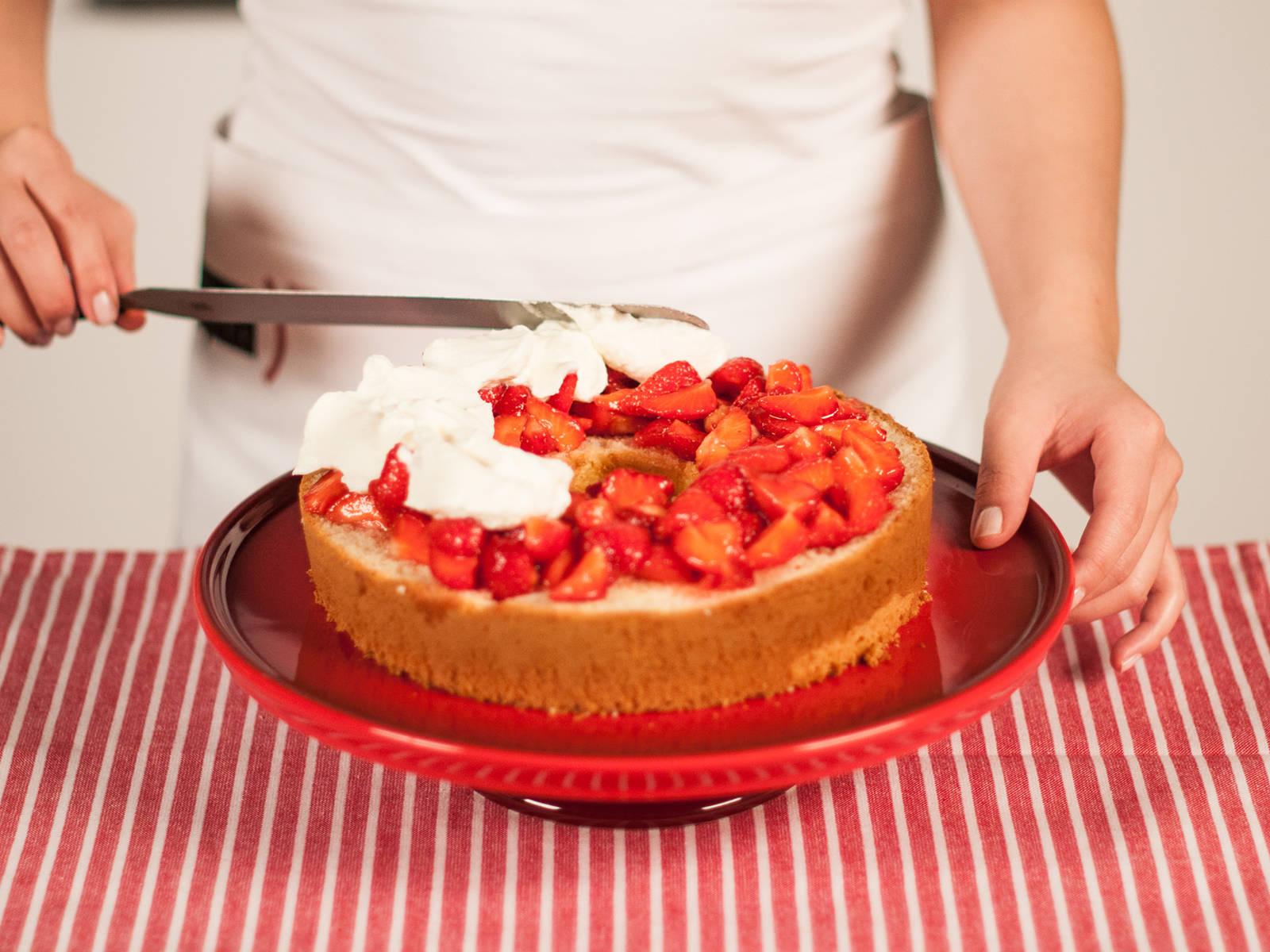 Den Kuchenboden auf einer Servierplatte anrichten. Mit der Hälfte der Erdbeeren belegen und mit Zitronensaft beträufeln. Die Sahne auf den Beeren verteilen und den nächsten Kuchenboden darauf platzieren.