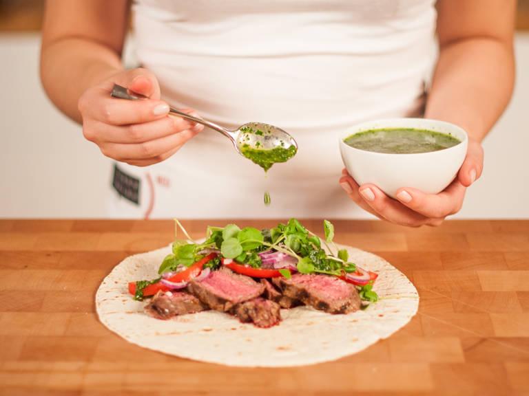 将切成片的裙带牛排放在墨西哥薄饼上。放上切片番茄、切片洋葱、西洋菜,淋上阿根廷青酱。卷好,佐以阿根廷青酱享用。